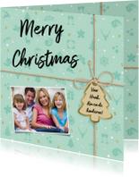 Kerstkaart als pakje met groene vormpjes in achtergrond
